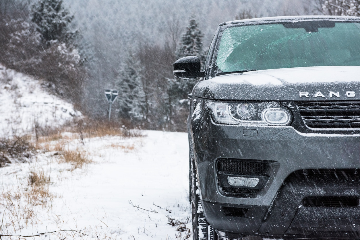 A Range Rover Sport 4x4 explores a wooded trail after a recent snow storm.