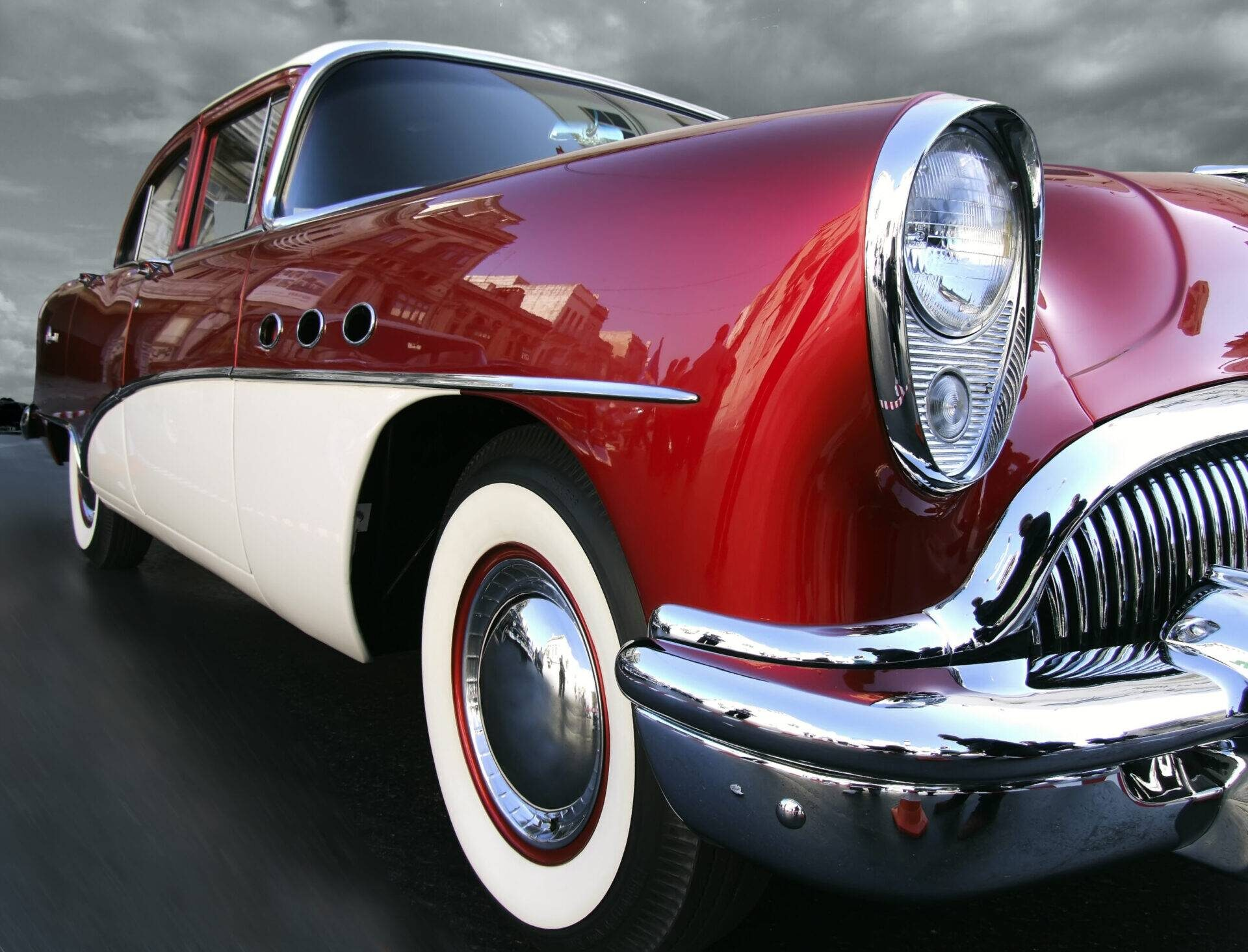Photograph of red American car featuring headlight and wheel